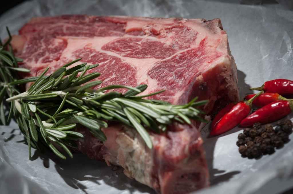 Steak de boeuf cru dans une assiette avec des piments rouges