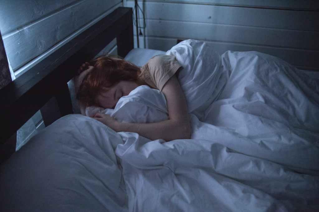 femme rousse qui dort sous sa couette